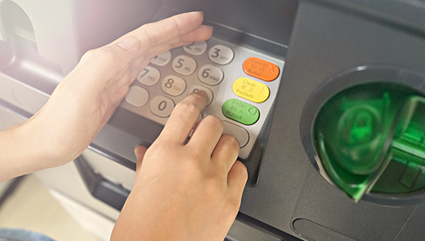 Person using their hand to protect their PIN at an ATM