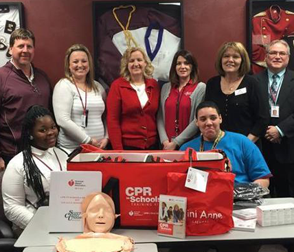 Belleville West High School and SCU Representatives post with one of the CPR kits donated