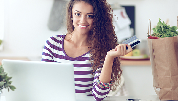 Woman in purple striped shirt holding a debit card while sitting at her laptop