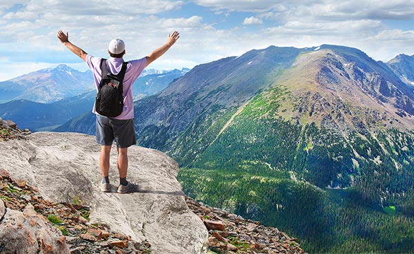 Man standing at a mountainous overlook. Take your checking to new heights.