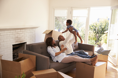 Family sitting on couch with moving boxes spread around