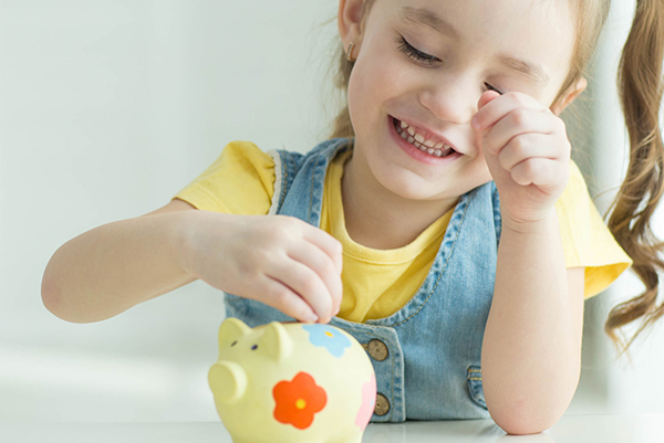 little girl putting money into a piggy bank