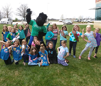 Scotty, the SCU Mascot, poses with a group of children
