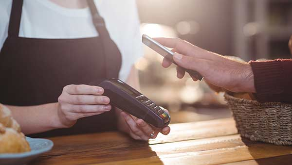 Person using Android Pay, Samsung Pay, or Apple Pay at register