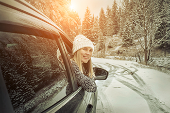 Woman looking out car window on a snowy road with a stocking cap on